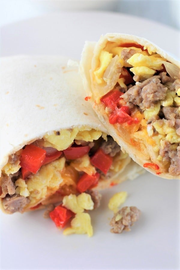 close up of a breakfast burrito cut in half on a plate