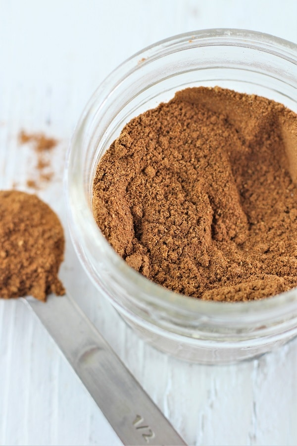 jar of homemade pumpkin pie spice with a measuring spoon full of spice on the side
