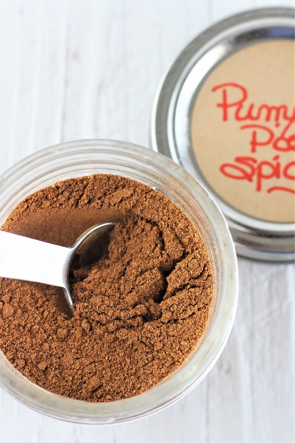 mason jar of pumpkin pie spice with a measuring spoon in it and a lid off to the side that says pumpkin pie spice