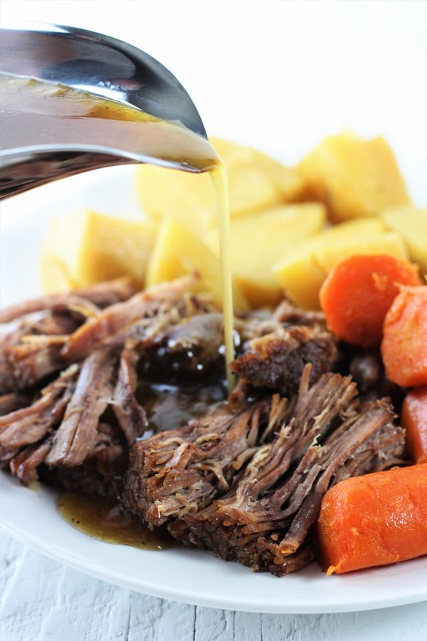 white plate of pot roast with carrots and potatoes with gravy being poured on