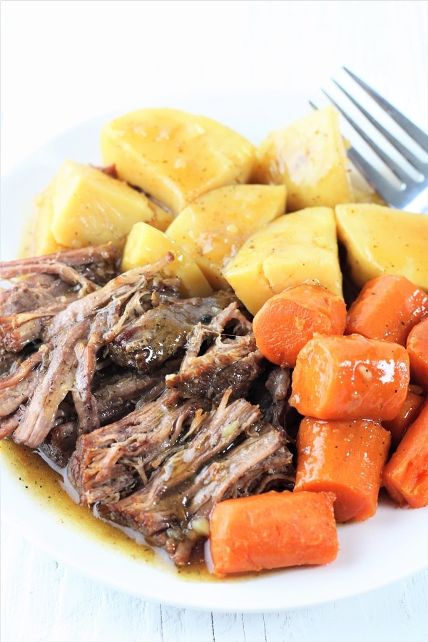 white plate and fork with pot roast, carrots, potatoes, and gravy
