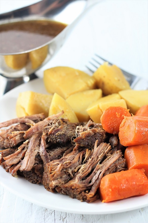 plate of pot roast, carrots, and potatoes with a bowl of gravy on the side