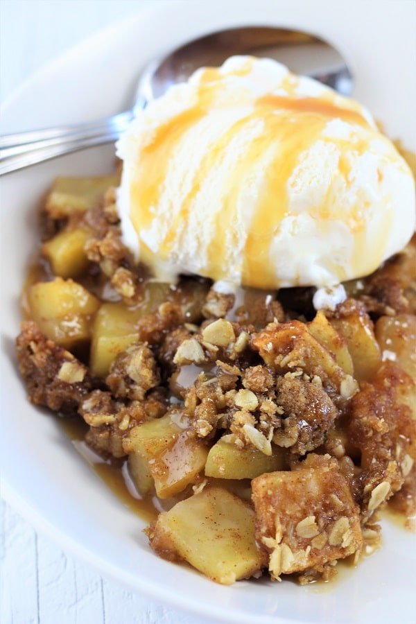 caramel apple crisp in a white bowl with a scoop of vanilla cream on top drizzled with caramel