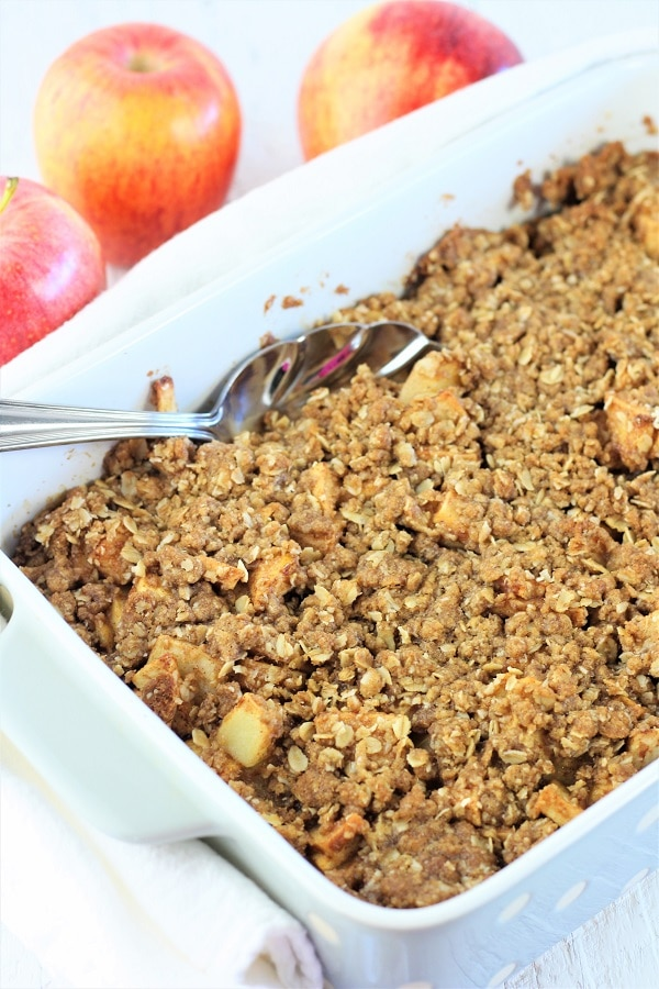 caramel apple crisp in a white baking dish with a serving spoon in it and apples in the background