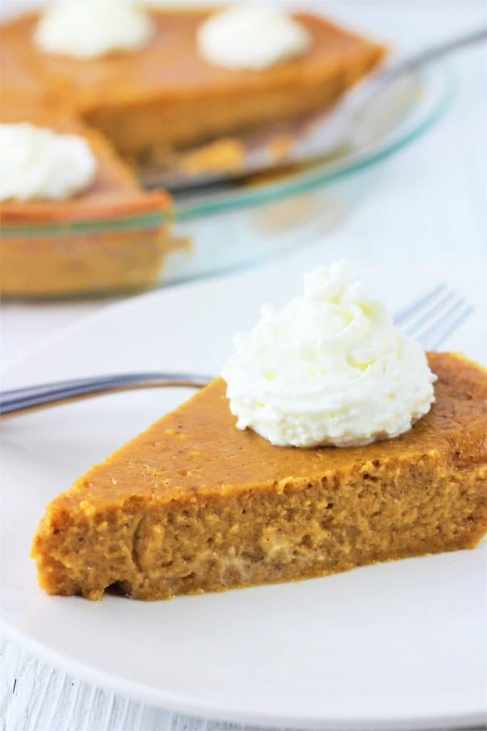 slice of crustless pumpkin pie with shipped cream on a white plate with a fork and the whole pie in the background