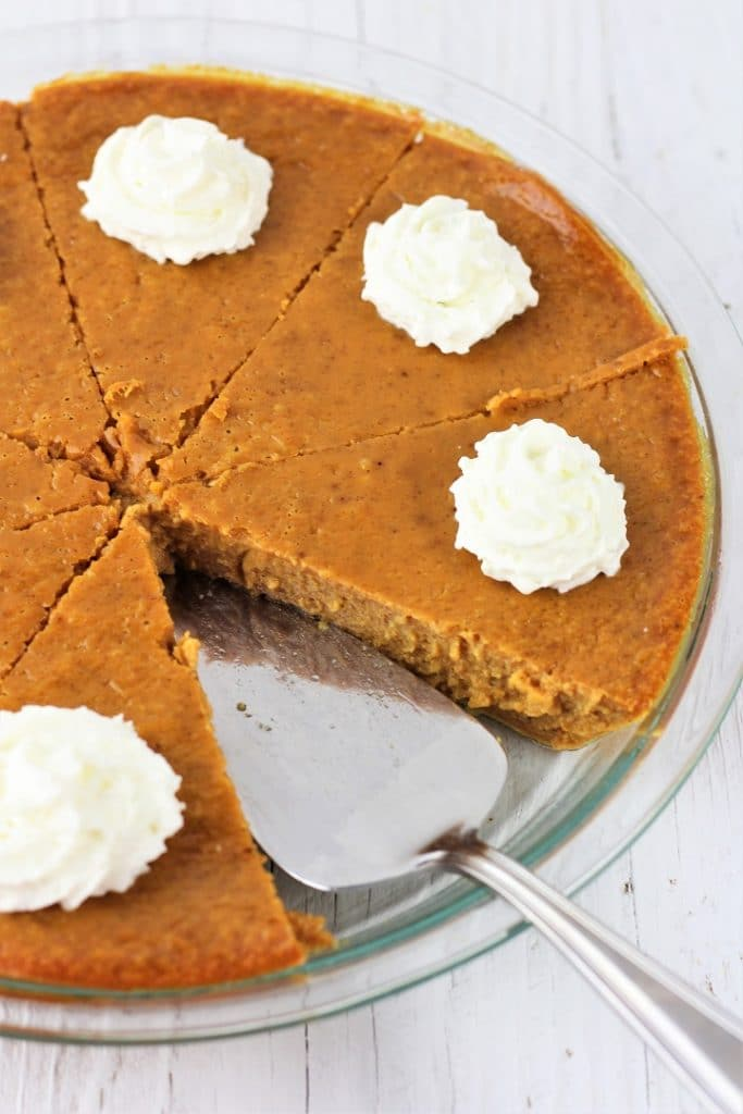 crustless pumpkin pie in a pie dish sliced into 8 pieces with a dollop of whipped cream on each piece