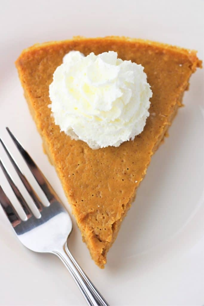 slice of crustless pumpkin pie with whipped cream on a white plate with a fork