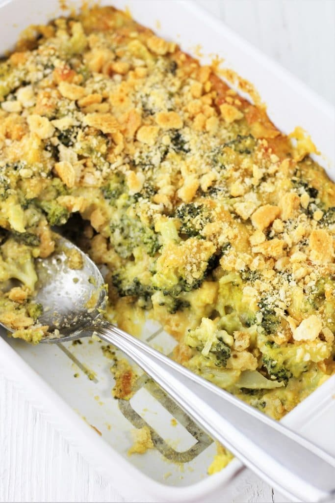 casserole dish of easy broccoli cheese casserole with some take out and a serving spoon in the dish