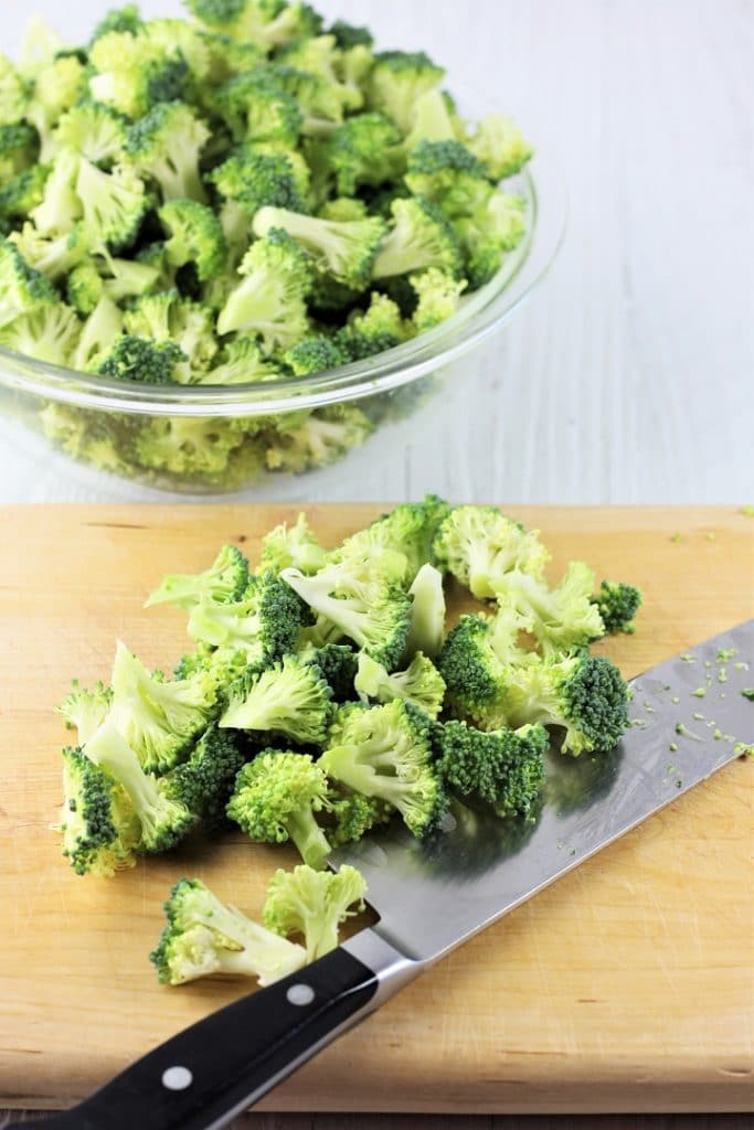 a wooden cutting board with chopped broccoli and a knife on it with a bowl of broccoli behind it