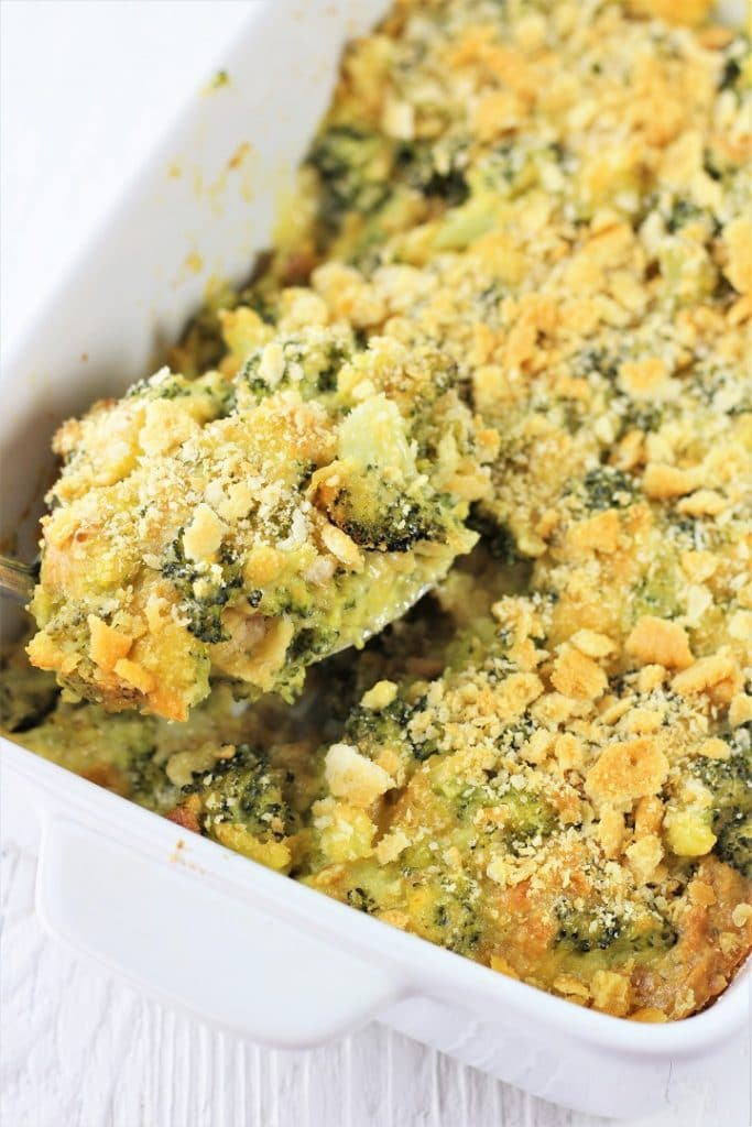 casserole dish of easy broccoli cheese casserole with a spoonful being taken out