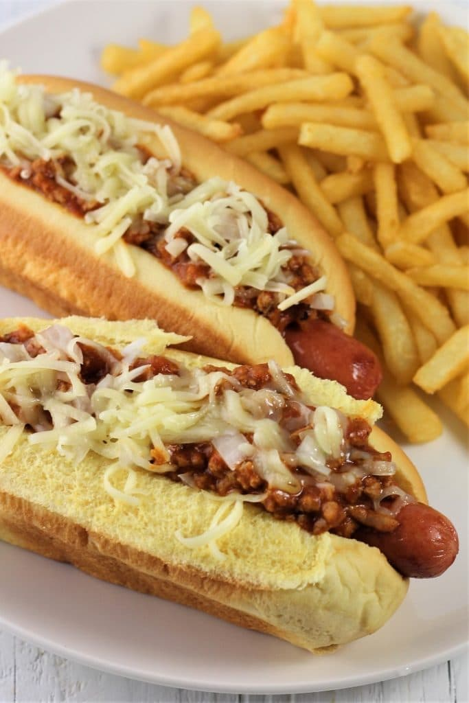 two chili cheese dogs on a white plate with french fries