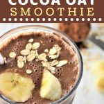 banana cocoa oat smoothie in a tall glass with a white straw and sliced banana and oats on top with a text overlay that says now cook this banana cocoa at smoothie