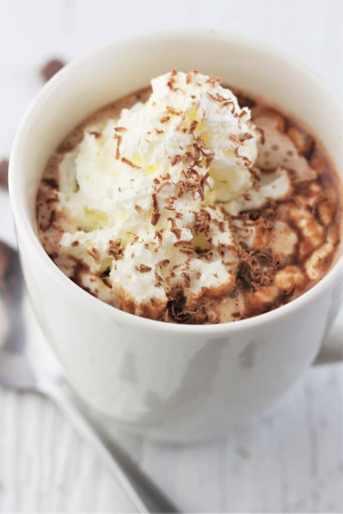 white mug of chocolate chip hot chocolate with whipped cream and chocolate shavings