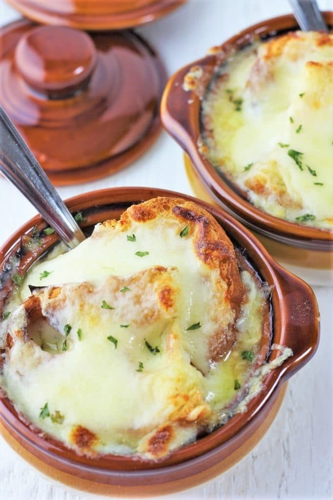 two bowls of french onion soup with spoons in them and the bowl lids off to the side