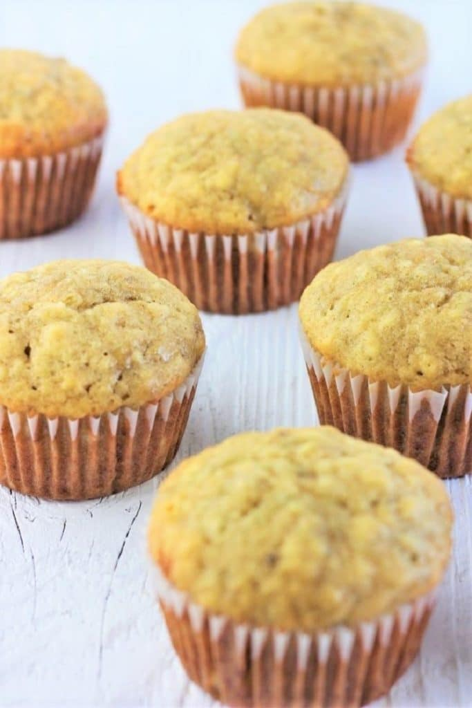 several banana bread muffins scattered on a table