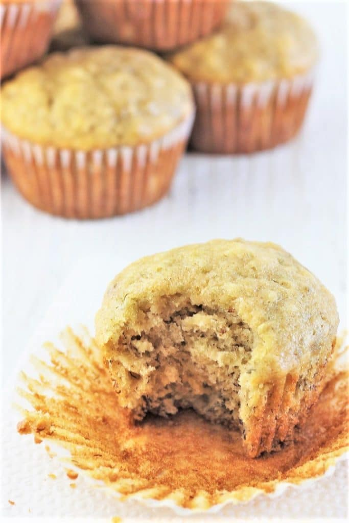 banana bread muffin with a bit taken out of it and a pile of muffins in the background