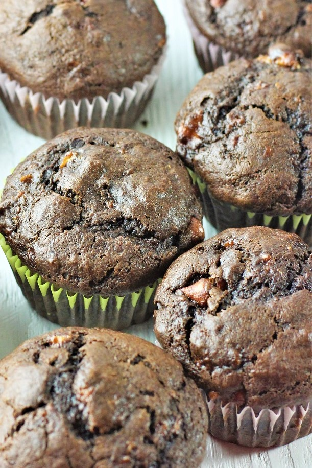 several chocolate banana bread muffins scattered on a table