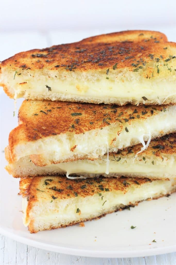 4 halves of a garlic bread grilled cheese sandwich stacked on a white plate