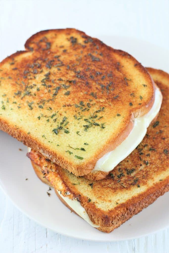 two garlic bread grilled cheese sandwiches stacked on a white plate