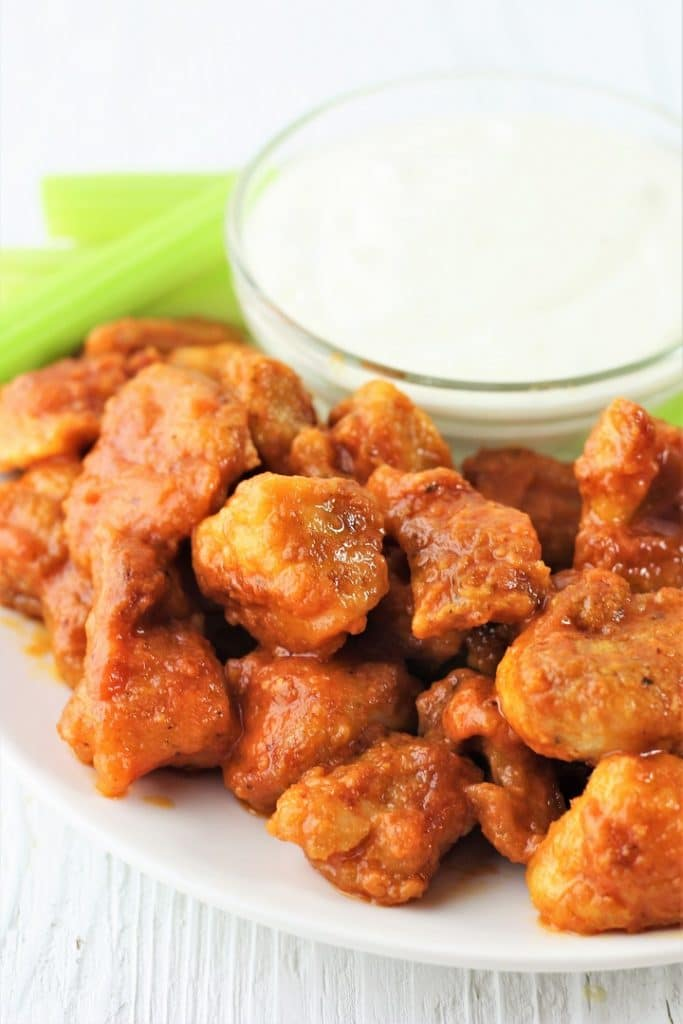 plate of buffalo chicken bites with celery sticks and a small bowl of blue cheese dressing