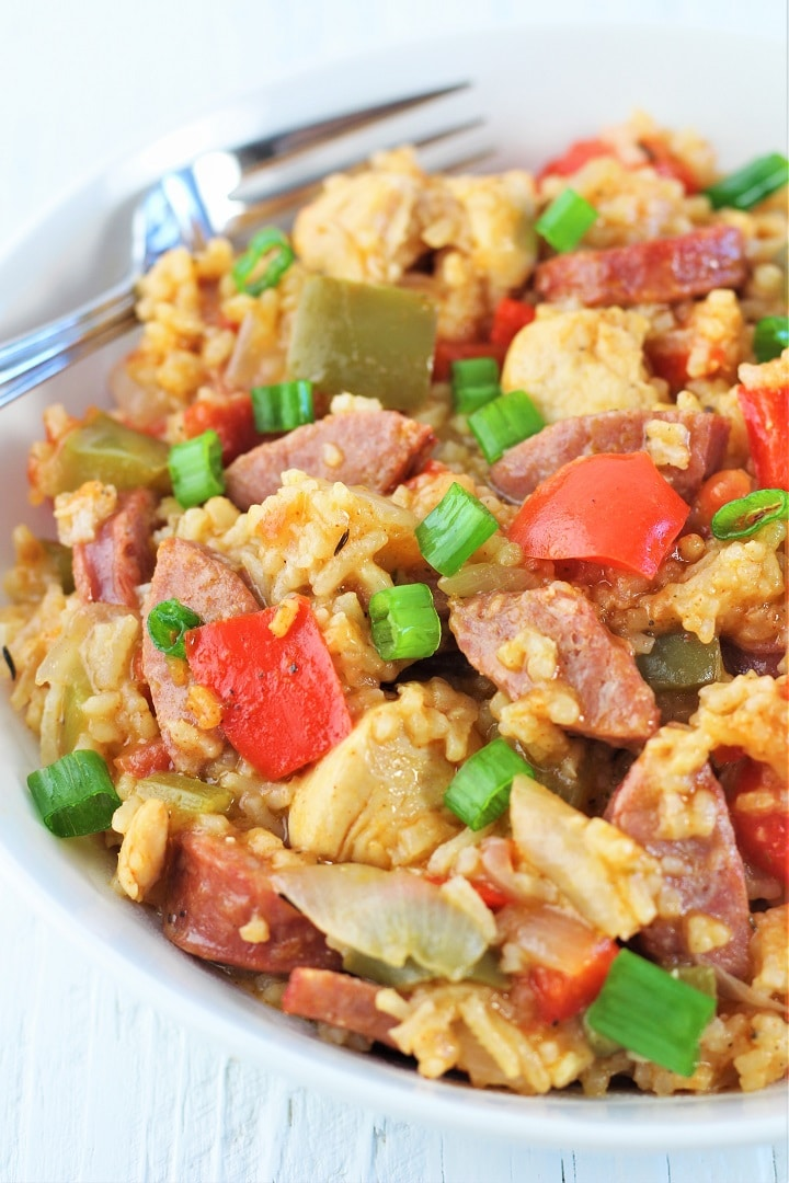 white bowl of chicken and sausage jambalaya with a fork