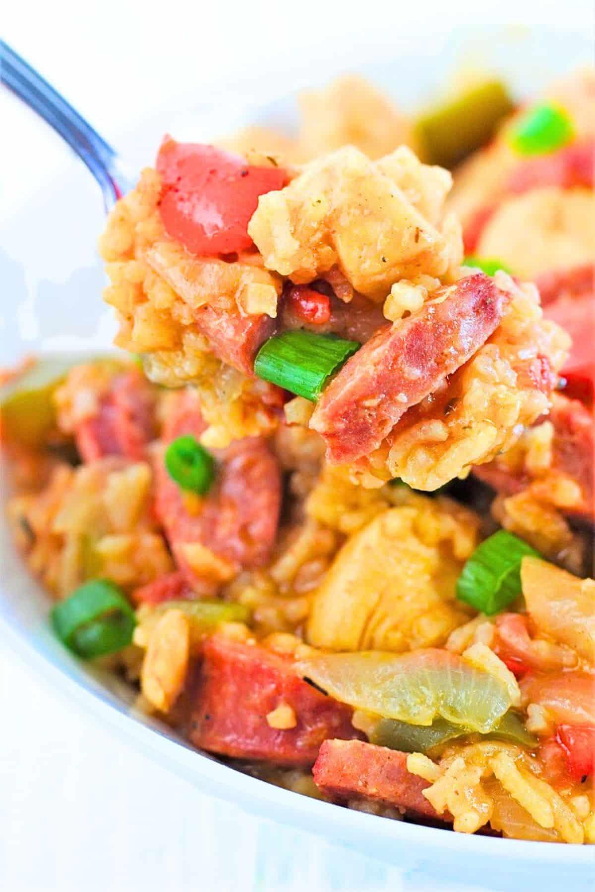 forkful of chicken and sausage jambalaya being taken out of a bowl