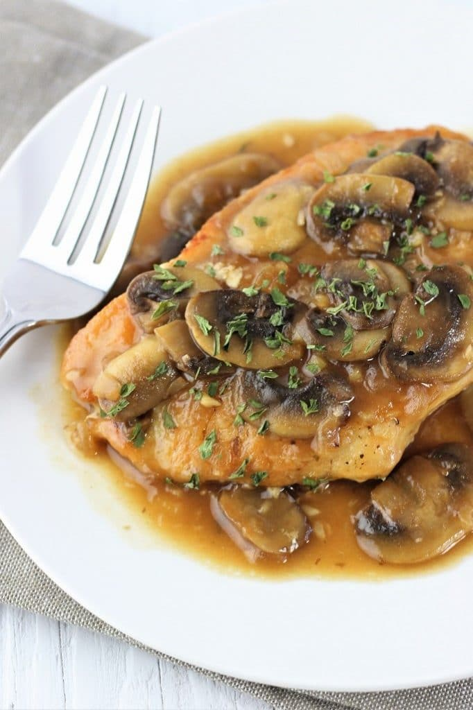 chicken marsala on with a fork on a white plate with a gray napkin underneath