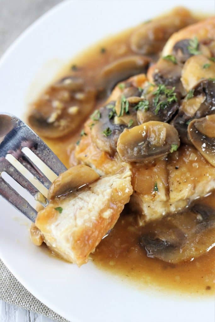 piece of chicken and a mushroom marsala on a fork being taken from a plate of chicken marsala