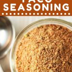 jar of taco seasoning and a measuring spoon with a text overlay that says now cook this easy homemade taco seasoning