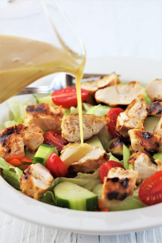 bowl of salad with chopped grilled chicken being drizzled with honey mustard dressing