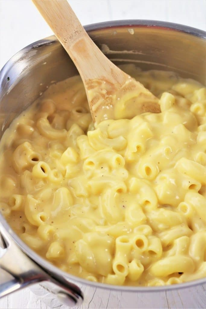 stove top macaroni and cheese in a pot with a wooden spoon
