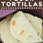 stack of flour tortillas in a tortilla warmer with a text overlay that says now cook this easy homemade flour tortillas