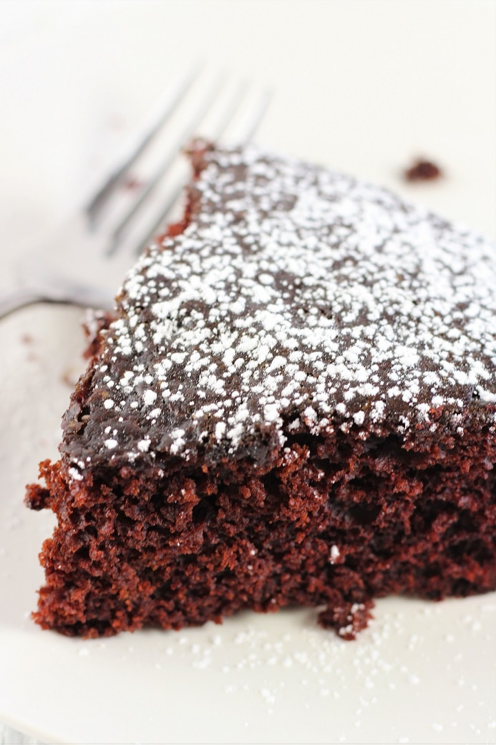 chocolate wacky cake on a white plate with a fork dusted with powdered sugar