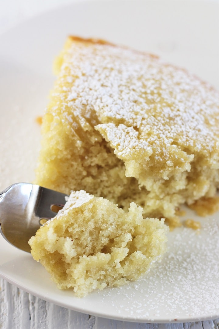 vanilla wacky cake on a white plate sprinkled with powdered sugar with a forkful being taken out