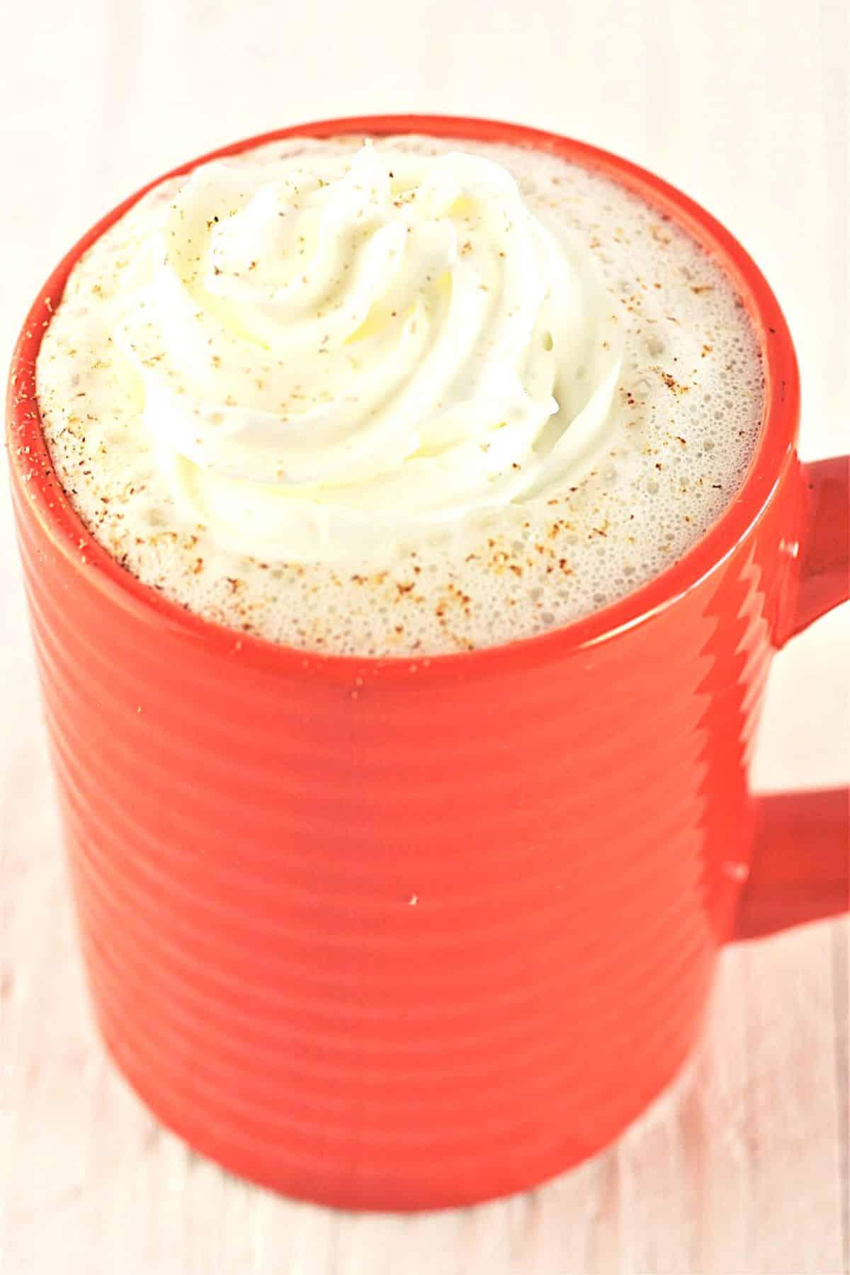 orange mug of warm vanilla milk bedtime drink with whipped cream and nutmeg