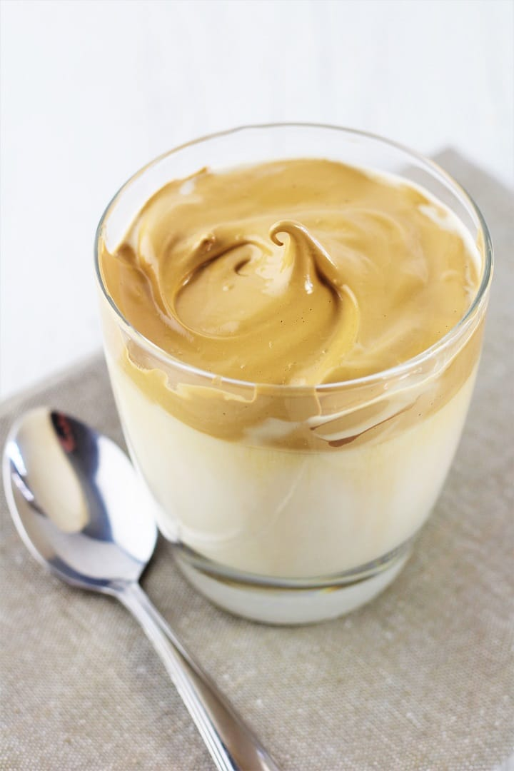 glass of caramel whipped coffee on a napkin with a spoon on the side