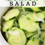 bowl of cucumber and onion salad with a spoon in it with a text overlay that says cucumber and onion salad nowcookthis.com