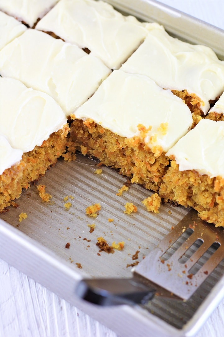 baking pan full of cut pieces of carrot cake with a spatula