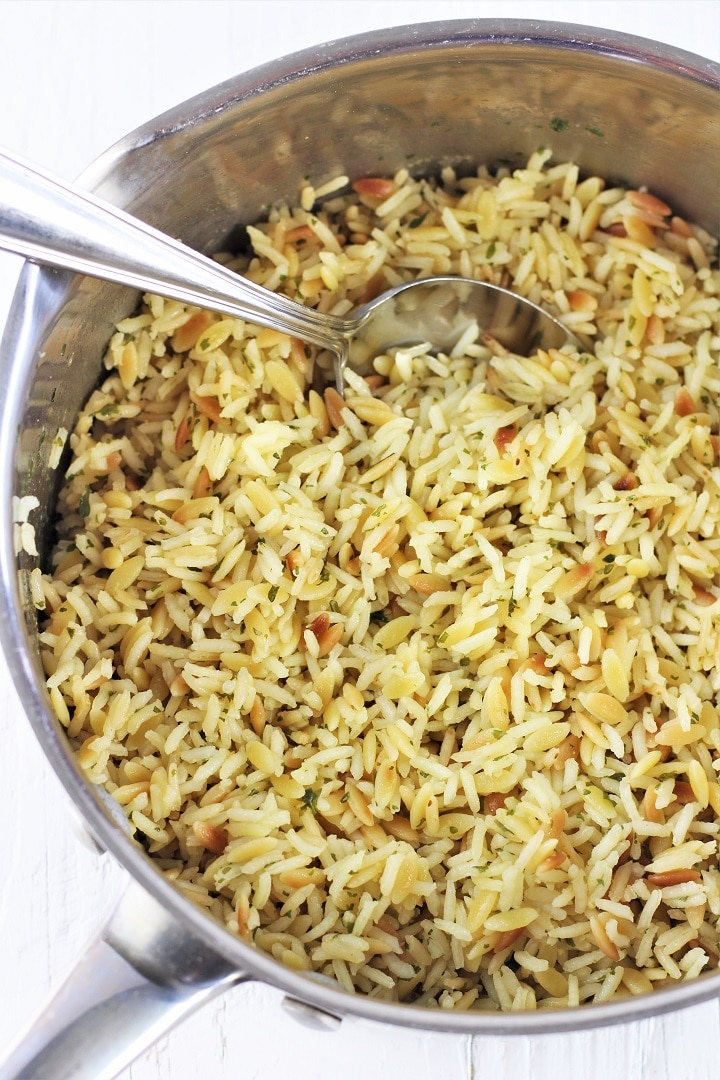 pot full of rice and pasta pilaf with a spoon in it