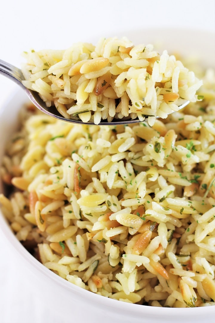 bowl of rice and pasta pilaf with a spoonful being held over it
