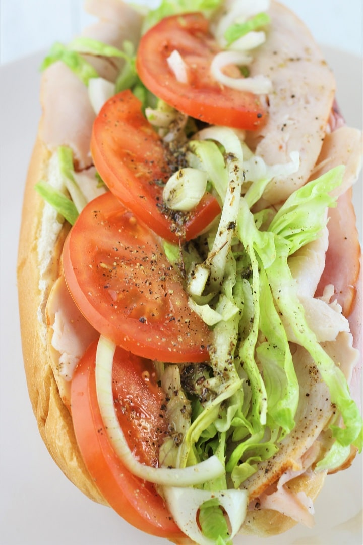 whole turkey italian hoagie on a white plate