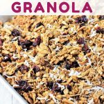 homemade granola on a baking sheet with a text overlay that says cranberry coconut homemade granola nowcookthis.com