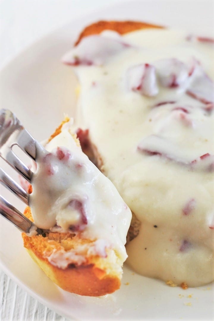 creamed chipped beef on toast on a white plate with a forkful being taken away