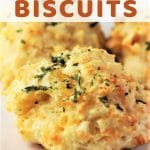cheesy garlic biscuits on a plate with a text overlay that says easy cheesy garlic biscuits nowcookthis.com