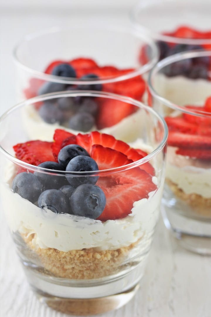 four easy no-bake cheesecake cups in clear glasses topped with strawberries and blueberries