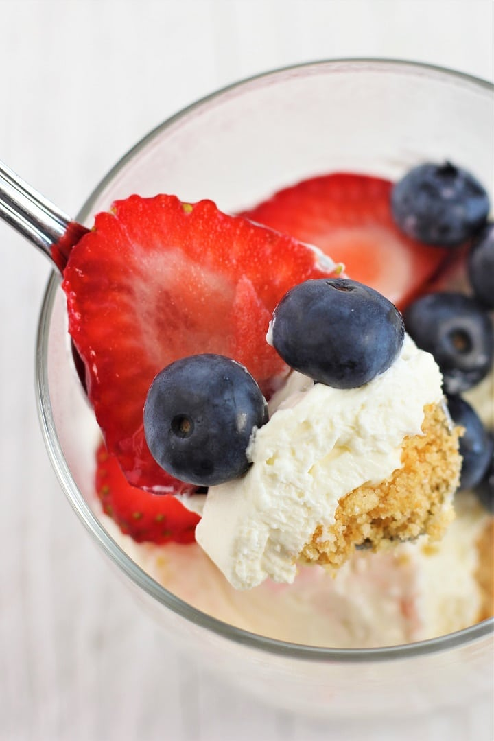close-up of a spoonful of easy no-bake cheesecake and berries being taken out of cup