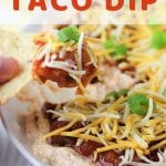 plate of taco dip with a chip being dipped into it with a text overlay that says quick and easy taco dip nowcookthis.com