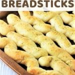 breadsticks on a baking sheet with a text overlay that says homemade garlic herb breadsticks nowcookthis.com