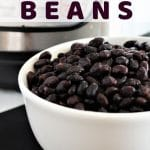 black beans in a white bowl with an instant pot in the background with a text overlay that says instant pot black beans nowcookthis.com