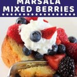 pound cake topped with berries and whipped cream with a fork with a text overlay that says now cook this pound cake with marsala mixed berries